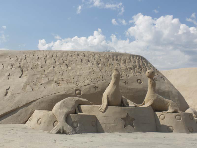 Kuva Lappeenrannan hiekkalinnalta. Hiekkapatsas, jossa kolme norppaa esittelevät temppuja ja leikkivät pallolla.