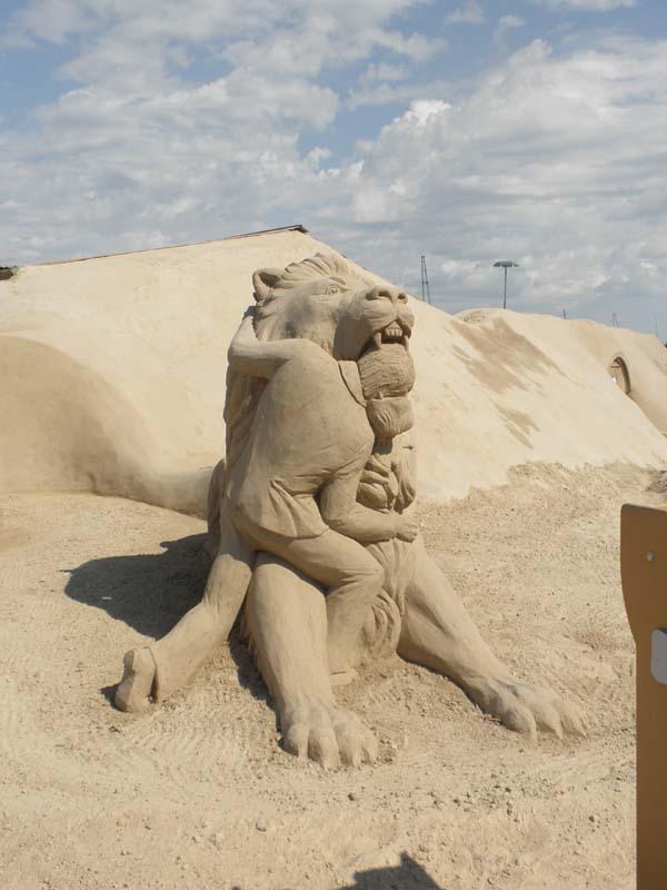 Kuva Lappeenrannan hiekkalinnalta. Hiekkapatsas, jossa ihminen halaa leijonaa ja työntää päänsä tämän suuhun.