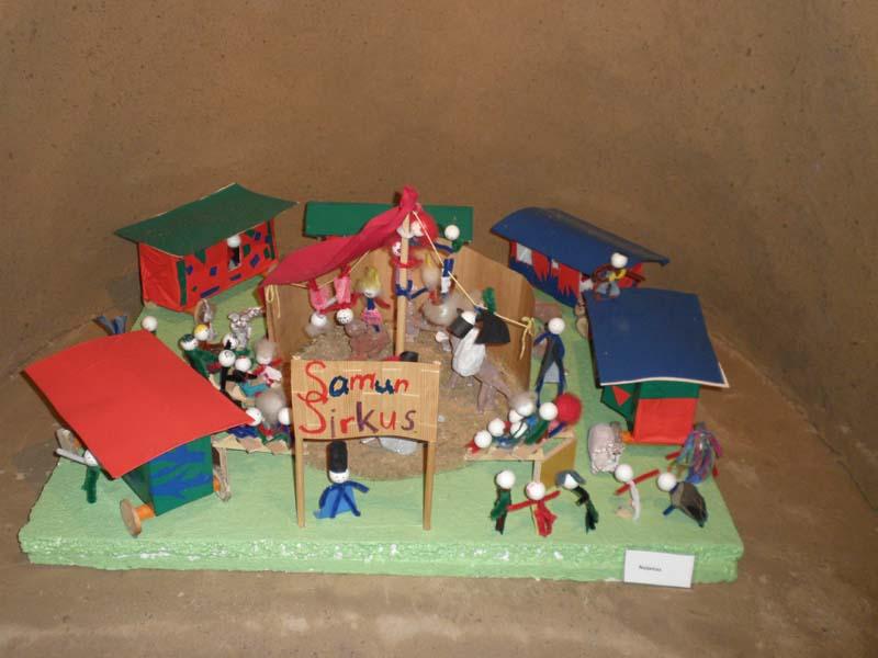 """Lähikuva lasten tekemästä sirkuspienoismallista, joka on esillä hiekkalinnan sisällä. Teoksessa """"Samun sirkus"""" on ihmishamoja, sirkuskojuja, eläimiä ja sirkusteltta."""