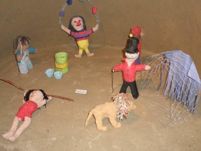 Lähikuva hiekkalinnan sisällä olevista, lasten tekemistä paperimassahahmoista. Hahmoina pelle, leijona ja leijonan kouluttaja.