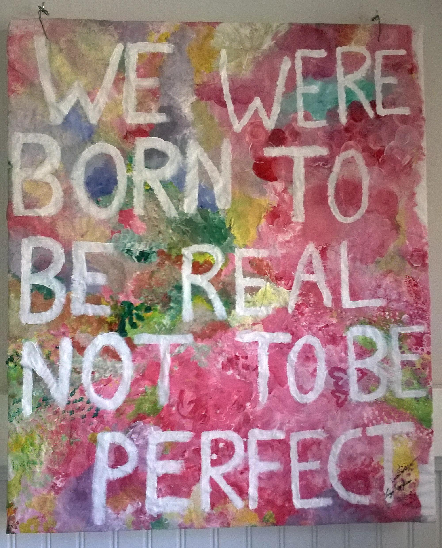 """Kuvassa Metkat-viikoilla tehty akvarellimaalaus, jossa monivärisellä taustalla valkoinen teksti """"WE WERE BORN TO BE REAL NOT TO BE PERFECT""""."""