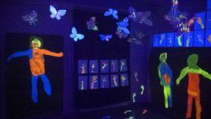 """Kuvassa Metkat-viikoilla toteutettu """"hehkuhuone"""". UV-valossa loistavia, lasten tekemiä maalauksia ihmishahmoista, käsistä, jaloista ja perhosista."""