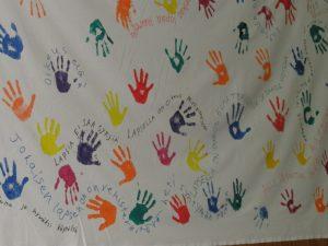 """Kuvassa Metkat-viikoilla maalattu, lasten oikeuksiin liittyvä valkoinen lakana. Lakanaan on painettu lasten käden kuvia eri väreillä sekä maalattu tekstejä, kuten: """"Lapsia ei saa syrjiä"""", """"Lapsella on oikeus mielipiteeseen"""" ja """"Lapsella on oikeus elää terveenä ja saada hoitoa""""."""